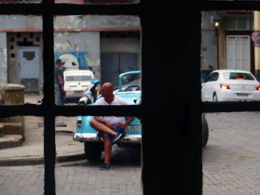 hombre cubano apoyado sobre su coche, fotografiado a través de una ventana