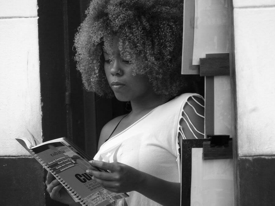mujer cubaba leyendo fuera de su negocio