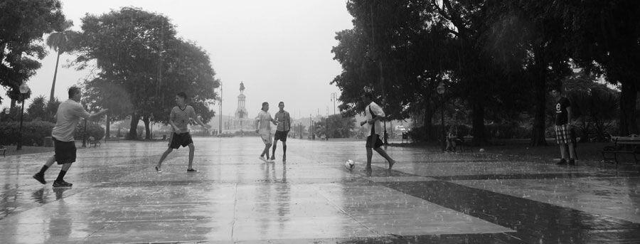 niños jugando al fútbol bajo la lluvia